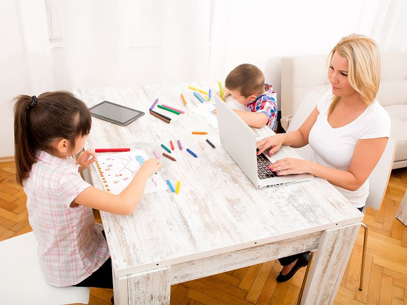 Woman working from home with children